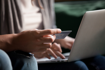 Paying money and buying online concept, couple doing internet shopping with computer, customers making secure payment on laptop via e-banking service, close up view of hand holding credit card