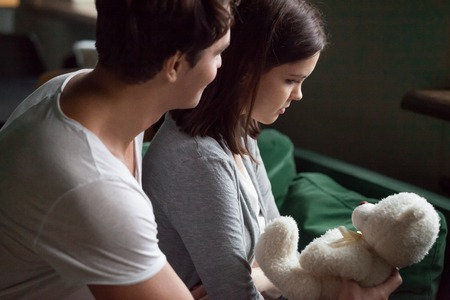 Boyfriend apologizing offended girlfriend presenting teddy bear toy asks for forgiveness expressing regret after fight making peace, caring husband supporting sad wife telling sorry, apology concept