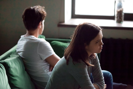 Disappointed frustrated millennial girlfriend and boyfriend avoiding each other offended after argument, resentful young couple sitting on sofa not talking feeling insulted and misunderstood concept
