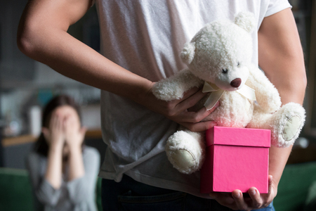 Man hiding pink gift box holding teddy bear toy behind his back making romantic surprise for wife or girlfriend waiting for unexpected present celebrating happy birthday concept, rear close up view