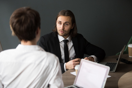 Back view from shoulder of businesswoman listening to millennial male partner talking during business meeting in boardroom, businessman explaining project strategy
