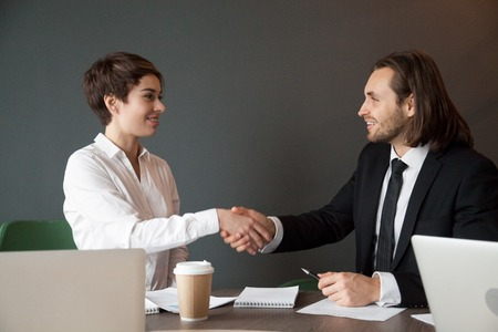 Business partners shaking hands after closing successful corporate deal at company meeting Stock Photo