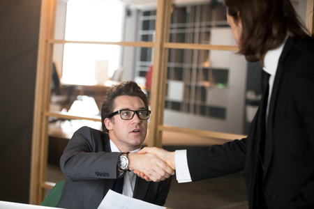 Middle aged businessman shaking hand of millennial male worker, greeting new manager in working team, newcomer handshaking CEO making good first impression during business meeting in office. Close up
