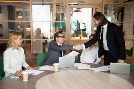 Middle aged CEO shaking hand of young male manager, greeting with job promotion, congratulating with work achievement, boss welcoming newcomer with handshake at business meeting room
