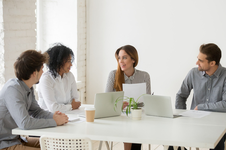 Multiracial coworkers discussing work contract at company business briefing in office, female businesswoman talking, sharing thoughts with colleagues, explaining new strategy. Cooperation concept Stock Photo