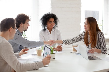 Colleagues handshaking greeting at business briefing, workers get acquainted at corporate multiracial team meeting, man congratulating female associate. Diversity, cooperation, interview concept Stockfoto