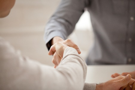 Close up of colleagues greeting with handshake, workers get acquainted at company briefing, worker shaking hand of associate congratulating, business partners closing deal. Cooperation, HR concept Stockfoto