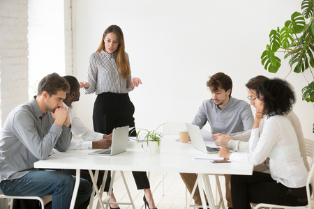 Serious businesswoman scolding employees for bad work results during company meeting, female team leader lecturing workers for poor financial rating at business briefing. Leadership concept Stock Photo