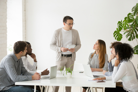 Serious male team leader making presentation to colleagues during company meeting, business coach taking opinion poll among employees at briefing, mentor conducting survey. Training concept