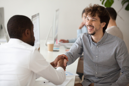 African American applicant shaking hand of Caucasian employee, thanking him for given job opportunity, smiling office worker handshaking black client. 写真素材