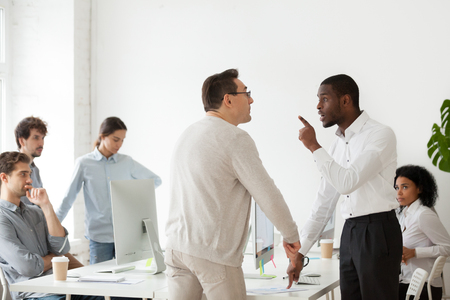 Angry African American worker arguing with Caucasian middle aged mentor, having disagreement over work issues, multiethnic colleagues disputing and quarreling loudly at shared workplace