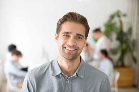 Portrait of casual smiling Caucasian male worker laughing looking at camera, positive employee posing for company business catalogue with colleagues at background