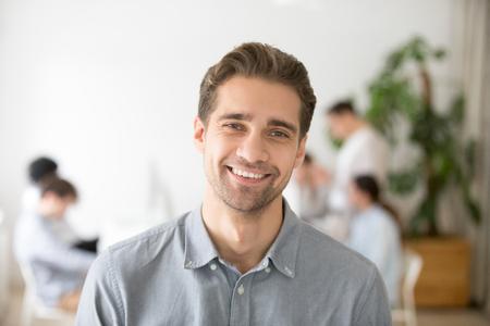 Portret van casual glimlachende blanke mannelijke werknemer lachen camera kijken, positieve werknemer poseren voor bedrijf bedrijfscatalogus met collega's op de achtergrond