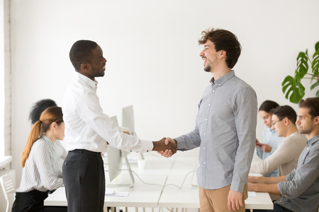 African American employer shaking hand of shy male Caucasian job applicant, congratulating with successful interview, greeting new member at workplace. Stock Photo