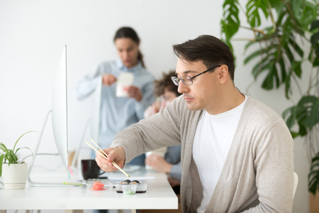 Middle aged male worker eating sushi at workplace while working at desktop computer, employee enjoying Japanese rolls spending lunch break at office desk.