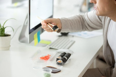 Close up of male employee eating Japanese sushi, holding roll with chopstick, having break at office desk, worker enjoying Asian food at workplace during lunch. Banco de Imagens