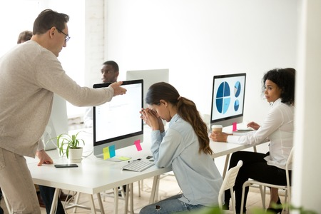 Angry middle aged CEO scolding and lecturing depressed young female worker in coworking shared office, sad upset woman listening to unfair accusations and blaming
