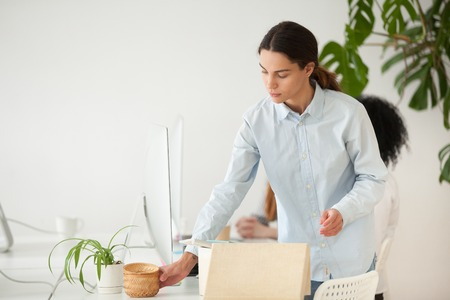 Concentrated young female worker unpacking box with personal items at new workplace, setting at desk in coworking office Stock Photo - 102620866