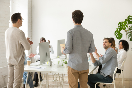 Back view of company CEO introducing male newcomer holding box on first day at work, colleagues laughing and applauding congratulating employee Stock Photo