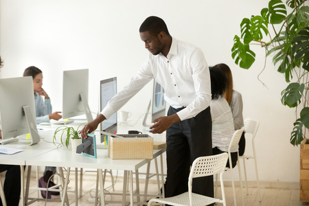 Focused African American employee unpacking box with personal items on first work day at new workplace, putting frame on office desk