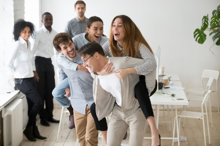 Smiling colleagues having fun, laughing and doing piggyback ride at workplace, coworkers playing games during work break or teambuilding meeting in office