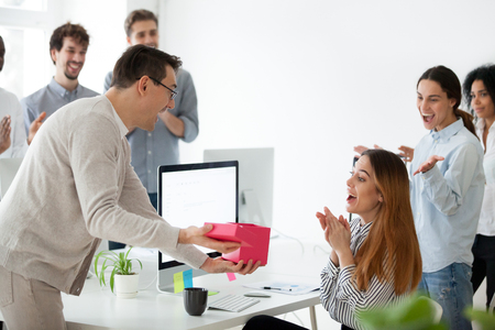 Excited male worker congratulating shocked female employee with special occasion, presenting gift box with unexpected surprise Archivio Fotografico