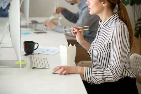 Focused female employee working at desktop computer while eating Asian takeaway food with chopsticks Stock Photo