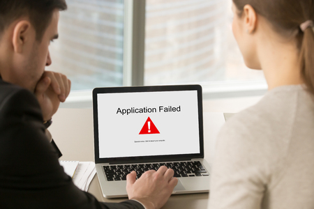 Two business people looking at laptop screen with Application Failed error message. Stock Photo