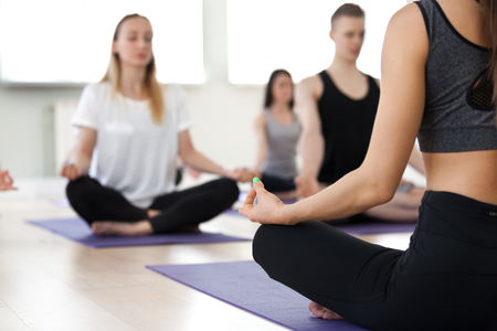 Group of young sporty people practicing yoga lesson with female instructor, doing Sukhasana exercise Stok Fotoğraf - 102620820