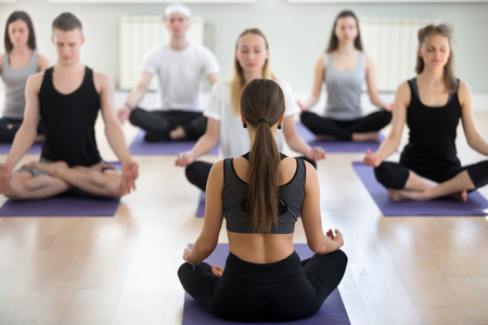 Group of sporty people practicing yoga with instructor, Easy Seat exercise, Sukhasana pose, working out, indoor session full length, students training, studio, teacher rear view.