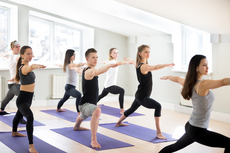 Group of sporty people practicing yoga lesson with instructor, doing Warrior Two pose, Virabhadrasana 2 exercise, indoor session close up, students working out in sport studio.