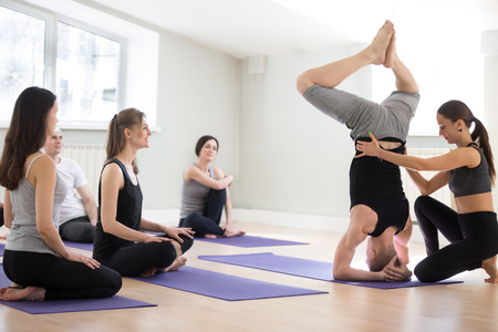 Young female yoga instructor helping male student with headstand pose, salamba sirsasana exercise, a group of sporty people practicing in studio, working out indoor, full length