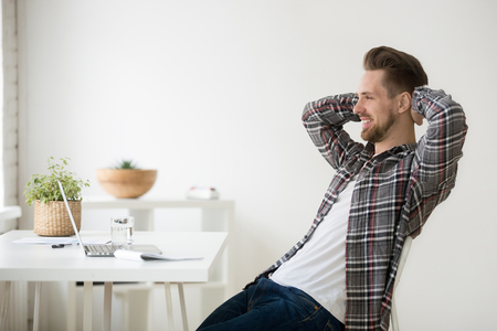 Satisfied Caucasian man relaxing leaning back in chair hands over head, happy with work finished, smiling after reading good online news at laptop