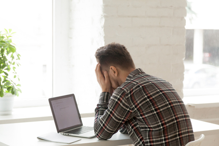 Depressed Caucasian worker feeling down, upset reading negative email about work termination, despaired manager being fired via computer.