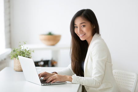 Portrait of beautiful Asian female office worker looking at camera smiling while working at laptop, young businesswoman posing for company catalogue near desk. Imagens