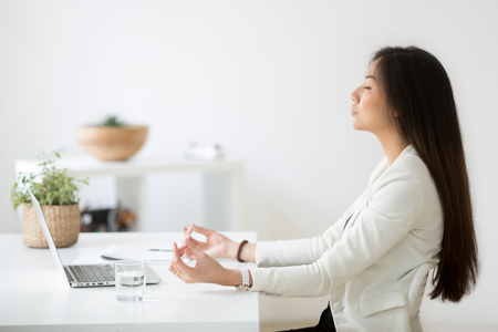 Calm thoughtful Asian female employee sitting at office desk meditating, practicing yoga, controlling emotions