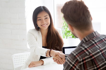 Back view of male hr shaking hand of smiling Asian job candidate, greeting with successful interview, female employee handshaking supervisor, making good first impression.