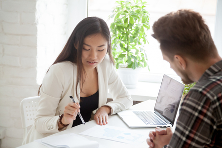 Female Asian supervisor explaining financial graphs to male colleague, talking on business issues, mentor coaching coworker, speaking on finances, partners discussing startup project. Teamwork concept Stockfoto