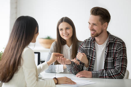 Back view of female real estate agent giving keys to smiling excited millennial couple, buying their first home together, deciding to move in, spouses becoming owners, purchasing apartment from broker