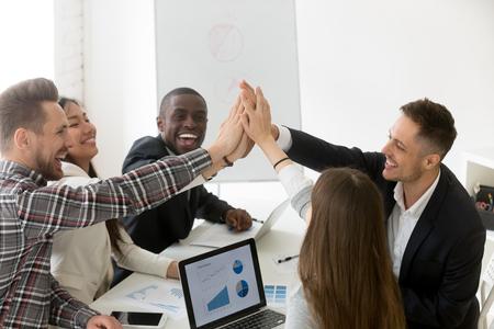 Opgewonden diverse millennial-groep die high five geeft om online zakelijke winst of gedeelde doelen te vieren, collega's feliciteren met goed resultaat, presterende teambuilding. Lonend concept Stockfoto