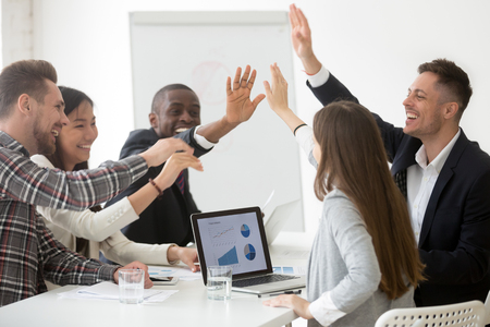 Excited diverse work team giving high five at board meeting, celebrating shared goal achievement, congratulating with win or good result, showing team spirit, unity. Concept of cooperation, rewarding Banco de Imagens