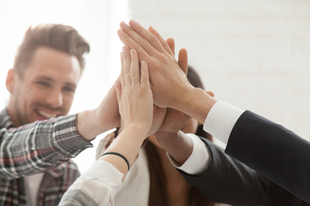 Close up of excited colleagues giving high five, celebrating shared goal achievement or win, performing team building, showing unity, workers greeting with successful project, good business results