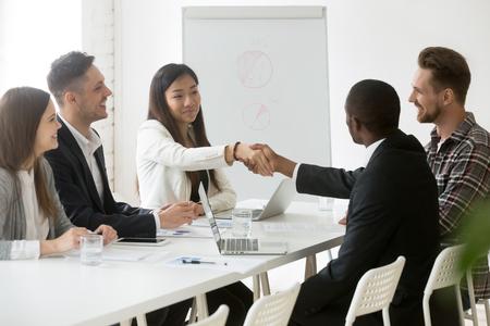 Uśmiechnięta azjatycka pracownica ściskająca rękę afroamerykańskiego kolegi na spotkaniu biznesowym w biurze, uścisk dłoni partnerów dziękując za udane negocjacje robocze. Koncepcja współpracy, partnerstwa