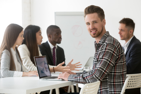 Portrait of smiling Caucasian male worker looking at camera while working at laptop at diverse team corporate business meeting, manager posing for photo during company briefing in office