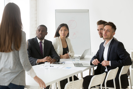Diverse millennial team looking judgmental at female worker being late to meeting, angry colleague scolding unpunctual coworker for not coming on time to briefing. Punctuality, time management concept Stock Photo