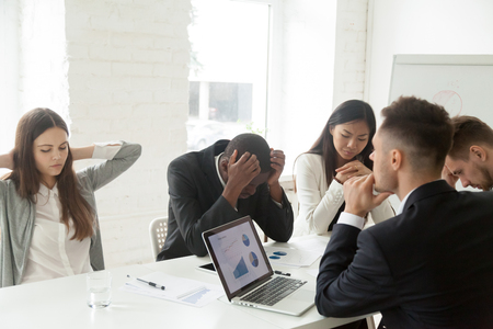 Disappointed diverse millennial team feeling despair because of bad results or falling statistics, upset colleagues shocked by negative bankruptcy news at company meeting, trying to solve problems.