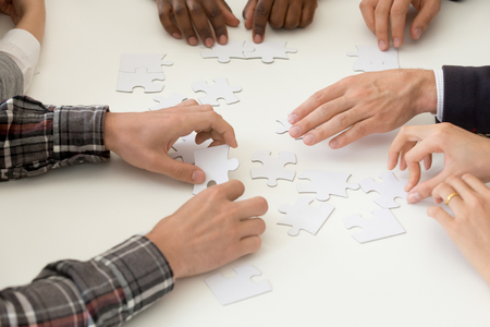 Close up top view of diverse work team assembling jigsaw puzzle together, involved in shared teambuilding activity, looking for business solution, helping to solve problem. Cooperation concept.