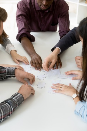 Top view of multiethnic workers involved in teambuilding activity, assembling jigsaw puzzle, showing trust and unity when finding best strategic way, looking for problem solution. Cooperation concept