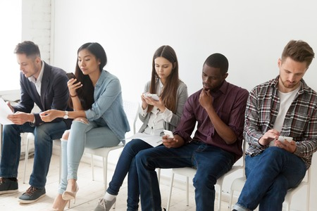 Serious diverse work candidates holding papers and electronic devices sitting in queue waiting for interview, applicants preparing for job talk or audition, reading cv or resume. Employment concept Stock Photo
