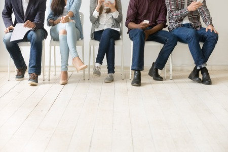 Close-up van diverse werkaanvragers die samen zitten, smartphones, tablets en papieren vasthouden die zich klaarmaken voor een interview, multi-etnische kandidaten die in de rij wachten. Werkgelegenheid, aanwervingsconcept Stockfoto